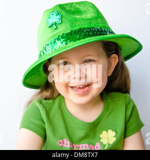 A smiling little girl dressed in green with a green hat celebrates St. Patrick's Day - Stock Photo