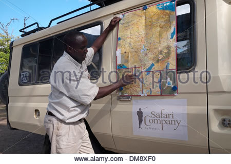 A jeep safari driver using the map to show location at the Ngorongoro conservation area in Tanzania eastern Africa - Stock Photo