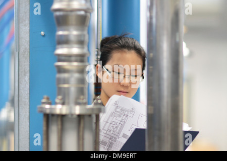 An Asia young woman working as a scientist in a technology lab - Stock Photo