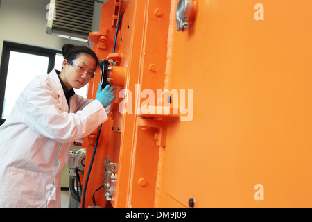 an asia woman scientist  working in a technolgy lab  between a machine and in front of a control window - Stock Photo