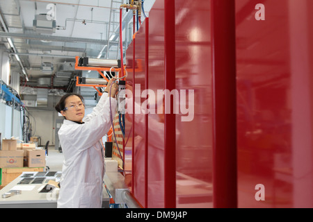 an asia woman scientist working in a lab with a lab coat on a technolgy mashine - Stock Photo