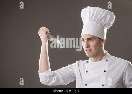 Portrait of smiling chef with in hand isolated on grey background - Stock Photo