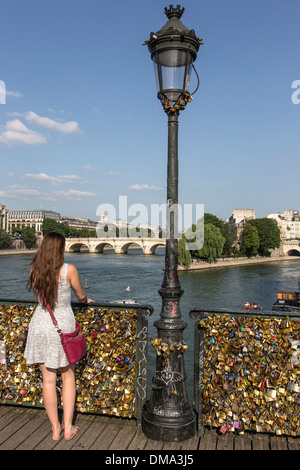 VIEW OF ILE DE LA CITE WITH THE PONT NEUF BRIDGE AND THE SQUARE DU VERT GALANT, YOUNG WOMAN IN FRONT OF THE PADLOCKS - Stock Photo