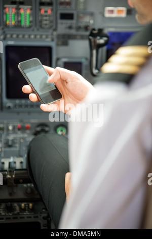 Pilots Using Smartphone In Cockpit - Stock Photo