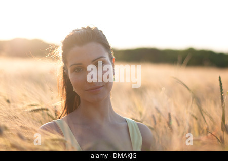 Young woman in dress standing in a corn field at sunset - Stock Photo