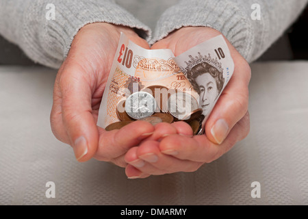 Hands holding English ten pound note and coins England UK United Kingdom GB Great Britain - Stock Photo