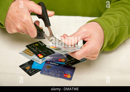 Cutting up credit card England UK United Kingdom GB Great Britain - Stock Photo