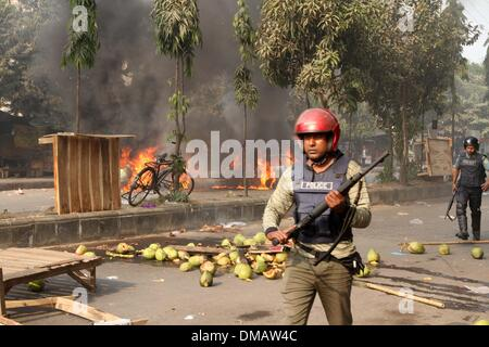 Dhaka, Bangladesh. 13th December 2013. Members of police run during a clash with the activists of Bangladesh Jamaat - Stock Photo