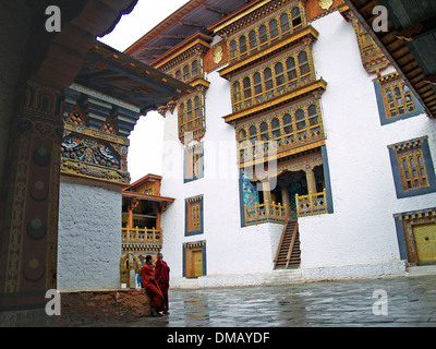 Two monks in the interior coutyard of the Punakha Dzong,Bhutan - Stock Photo