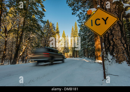 Road icing warning yellow sign on a snowy road, Yosemite National Park, California, USA - Stock Photo