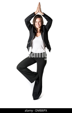 Business woman in black suit performs a yoga exercise on white background - Stock Photo