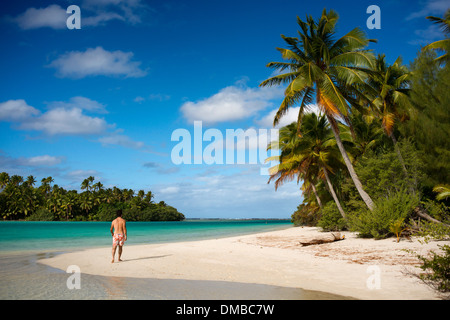Aitutaki. Cook Island. Polynesia. South Pacific Ocean. A tourist walks along the edge of the palm-fringed beach - Stock Photo