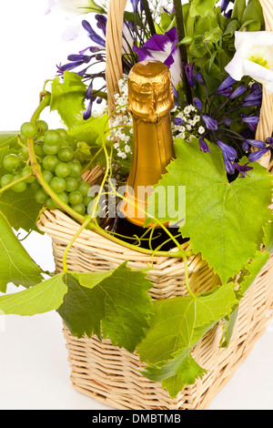 A still life of flowers in a basket with champagne and a white grape vine - Stock Photo