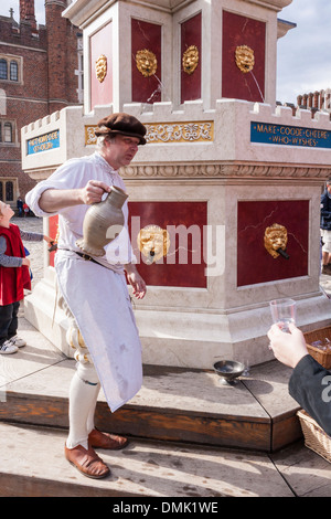 Actor in period costume serves glasses of wine at the Henry VIII wine fountain in Base Court at Hampton Court Palace. - Stock Photo