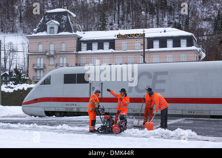WORKERS FOR THE SWISS FEDERAL RAILWAY CLEARING SNOW FROM THE PLATFORM AT THE INTERLAKEN OST STATION WITH AN ICE - Stock Photo