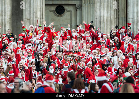 London, UK. 14th December, 2013.  Hundreds of Santas gathering on the steps of St Pauls Cathedral before they march - Stock Photo
