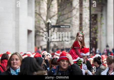 London, UK. 14th December, 2013.  A young girl being carried on her father's shoulders as part of the annual Santacon - Stock Photo