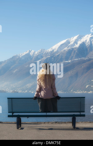 a girl in a pink coat is sitting on a bench at a lake - Stock Photo