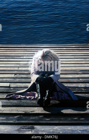 a blond girl in a pink coat is sitting on a wooden footbridge - Stock Photo