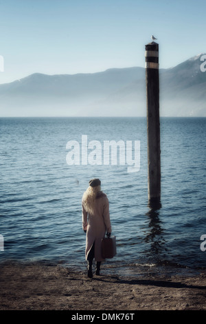 a woman in a pink coat is walking into the lake with a suitcase - Stock Photo