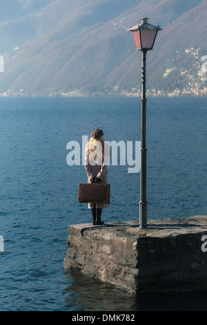 a woman in a pink coat is standing on a jetty at a lake - Stock Photo