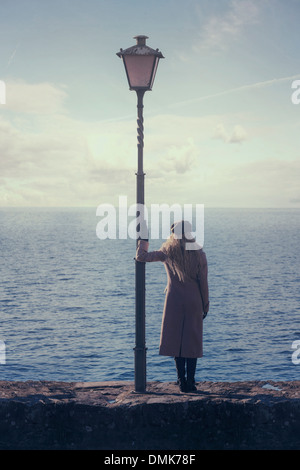 a woman in a pink coat is standing next to a lantern at the sea - Stock Photo
