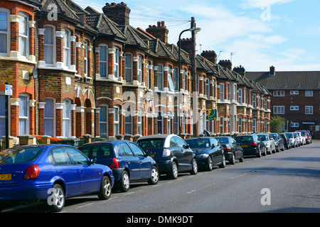 Typical East London terraced housing with residents car parking spaces in street - Stock Photo