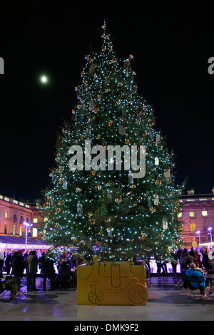 Somerset House Christmas tree and floodlit facades around temporary winter ice skating rink - Stock Photo