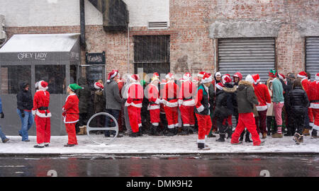 Santas and their elves outside the Grey Lady bar in the Lower East Side neighborhood of New York during the annual - Stock Photo