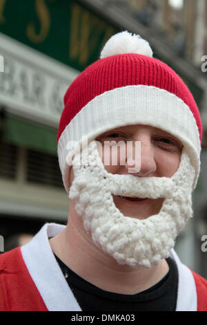 London, UK, 14th Dec, 2013.  A man with a special warm crochet Santa beard defies winter weather during Santacon, - Stock Photo
