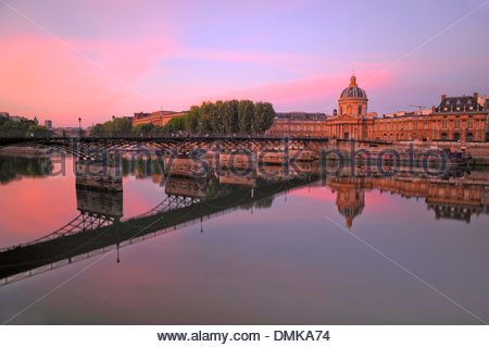 Paris on the Seine river during a warm sunrise; featuring the Pont des Arts or Passerelle des Arts and the Institut - Stock Photo