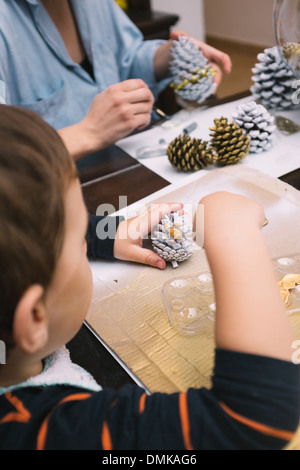 Little boy and his mother are painting pine cones for Christmas - Stock Photo