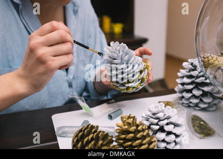 Woman painting pine cones at her home - Stock Photo