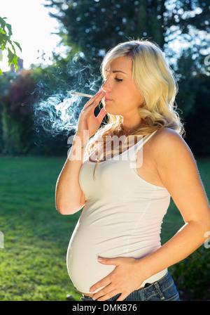 pregnant woman smoking a cigarette - Stock Photo