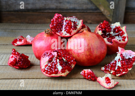ripe pomegranates on a rustic table, food closeup - Stock Photo