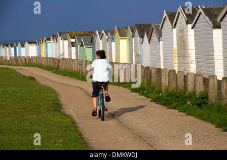 Cyclist passing beach huts on coastal cycle route(part of National Route 2) Lancing, West Sussex,UK. Lancing Beach - Stock Photo