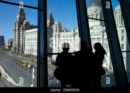 Visitors looking out of window of Museum of Liverpool towards Liver Building on Pier Head, Liverpool, Merseyside, - Stock Photo