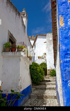 Narrow street / alleyway in old walled town of Obidos, central Portugal. Town wall beyond. - Stock Photo