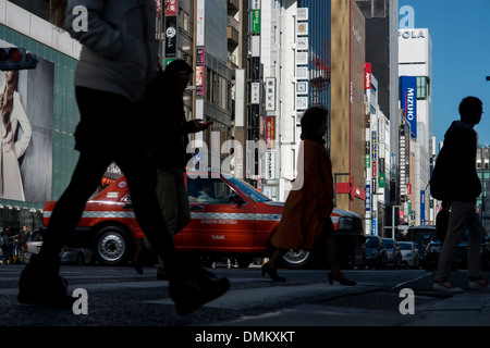 Pedestrians cross the road in Shinjuku, a major high end shopping district in Tokyo, Japan. - Stock Photo