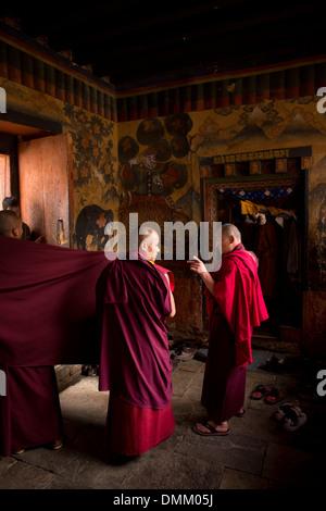 Bhutan, Bumthang Valley, Jambey Lhakang, two Buddhist monks inside monastery - Stock Photo