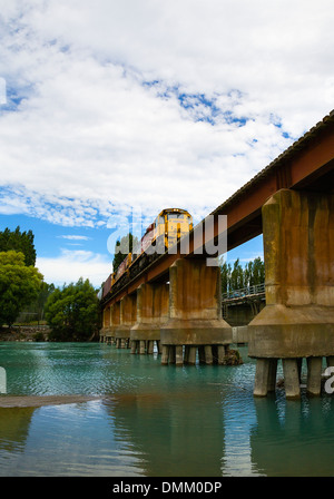 Kiwirail train on a bridge over the Waimakariri river, near Christchurch, Canterbury, South Island, New Zealand - Stock Photo