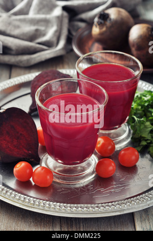 Beetroot smoothie in glass with fresh vegetables on round tray - Stock Photo