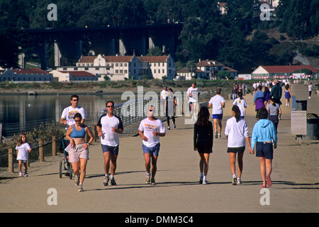 People running and walking on path at Crissy Field in the Presidio, San Francisco, California - Stock Photo