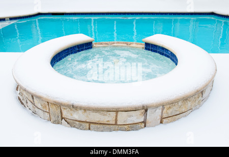 Outdoor residential hot tub or spa by swimming pool surrounded by snow in the winter - Stock Photo