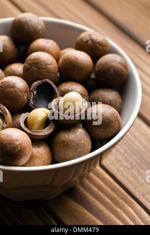 macadamia nuts in ceramic bowl - Stock Photo