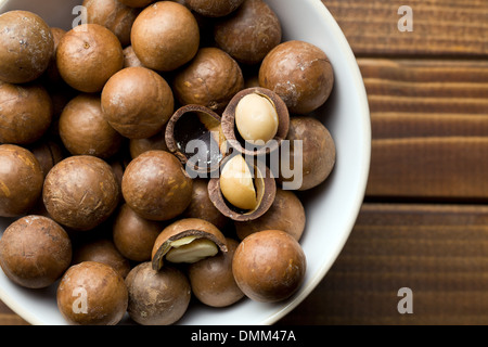 top view of macadamia nuts in ceramic bowl - Stock Photo