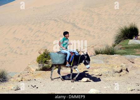 Berber boy riding a donkey a small valley near a Berber village on the coast south of Essaouira Morocco - Stock Photo