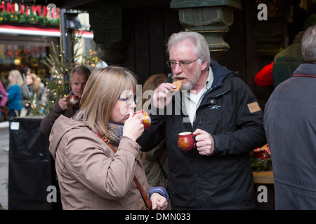 Christmas Market  Cologne: Couple drinking Glühwein or mulled wine in the Altstadt (old part of the city) - Stock Photo