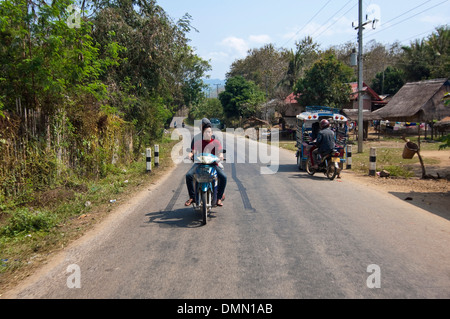 Horizontal portrait of two local Lao guys riding a motorbike along the road without helmets in the Laos countryside. - Stock Photo