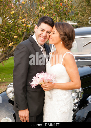 Bride and groom with funny expression outdoors - Stock Photo